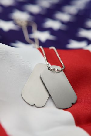 Vertical blank dog tags on American flag with focus on tags - Shallow dof photo