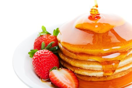 上に注がれるパンケーキとメープル シロップの重い量とイチゴ