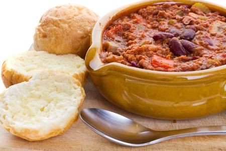bowl of chili con carne with crusty buns and spoon photo
