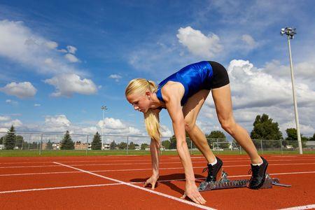 Jonge atleet in de start blokken klaar om te racen