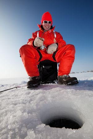 Happy fisherman fighting a fish while ice fishing photo