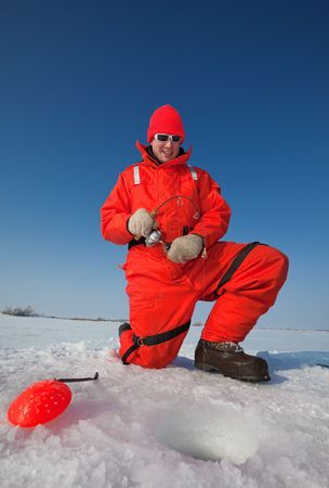 smiling ice fisherman fighting a big fish through the ice photo