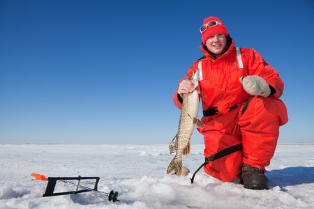 Happy ice fisherman holding a northern pike caught on a tip up Zdjęcie Seryjne - 6411780