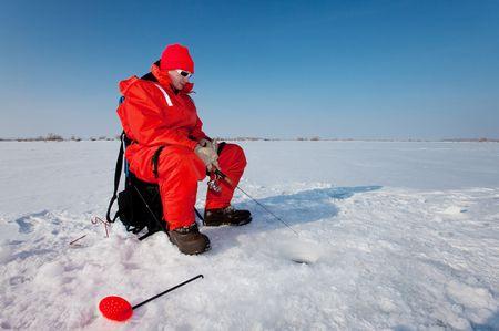 漁師が氷上で釣りの日を楽しんで