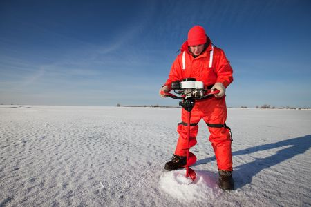 Ice fisherman drilling a hole with a power auger on a frozen lake