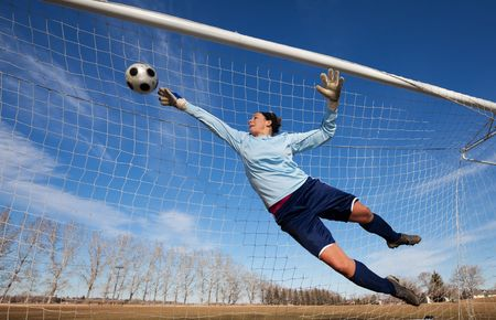 A female soccer player diving to catch the ball photo