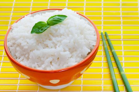 Bowl of steamed rice on yellow with bamboo chopsticks  photo