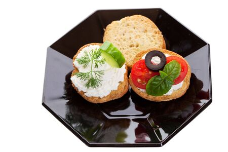Two canapes with goat cheese, garnished with dill and basil on a black plate photo