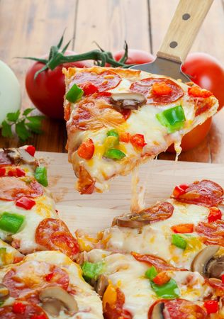 gourmet pizza: Slice of supreme pizza being lifted up Stock Photo