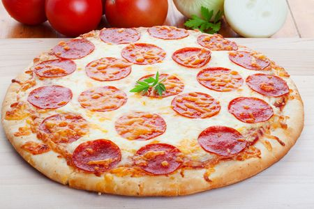 玉ねぎとトマトではバック グラウンドで木にペパロニのピザのクローズ アップ