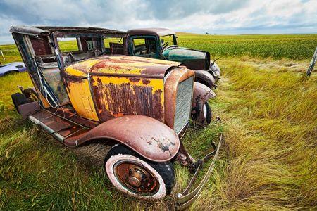 Vintage auto en truck overgelaten aan roest in een boeren veld  Stockfoto