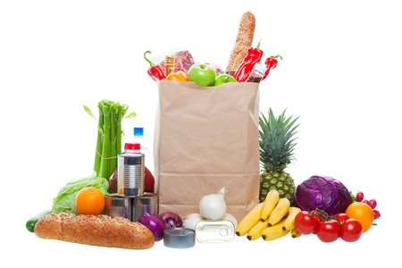 A paper bag full of groceries, surrounded by fruits, vegetables, bread, bottled beverages, and canned goods. Studio isolated on White background