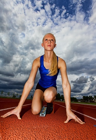 A teenage track athlete in the starting blocks with dramatic sky in the background 免版税图像