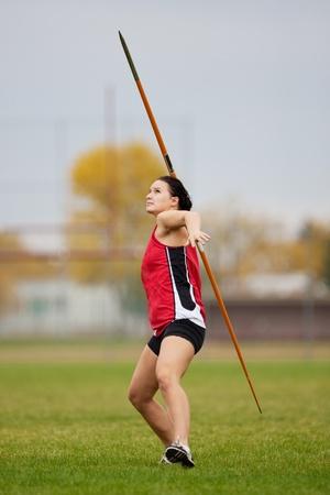 lanzamiento de jabalina: Atleta femenina lanzando una jabalina en un evento de deportes de pista y campo Foto de archivo