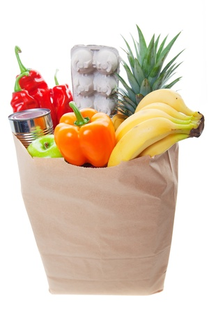 A grocery bag with eggs and healthy fruits and vegetables, Main Focus on front of bag  photo