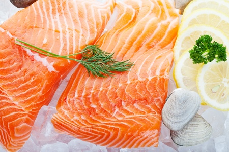 Fresh fillets of salmon on ice with Parsley, clams and lemon