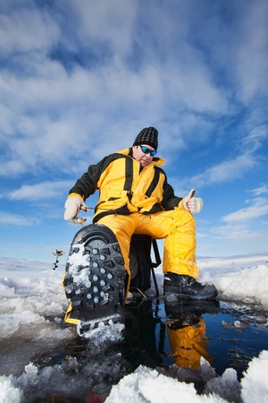 Happy fisherman in winter ice fishing photo