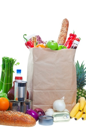 A paper bag full of groceries, surrounded by fruits, vegetables, bread, bottled beverages, and canned goods. Studio isolated on White background  photo