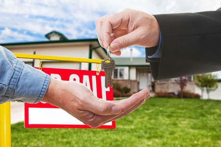 A  realtor handing over keys to a buyer infront of a house