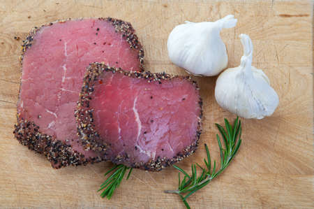 butchered: Two raw, eye of round, Alberta beef steaks, with pepper & garlic with fresh rosemary.  Stock Photo