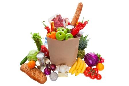 食料品、果物、野菜、パン、ボトル入りの飲料、缶詰商品に囲まれての紙袋。白い背景で隔離のスタジオ。