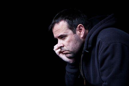 depressed man: A depressed man contemplating his future, shot on black.
