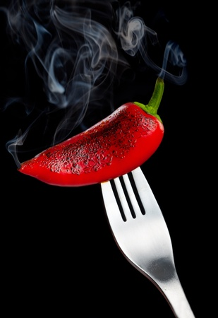 heartburn: Smoking hot pepper on a fork over black background