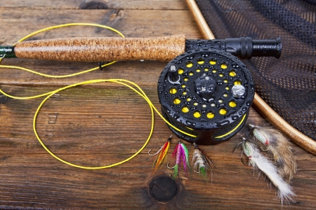 baits: fly fishing rod and reel on a wet wooden background, focus on the reel.