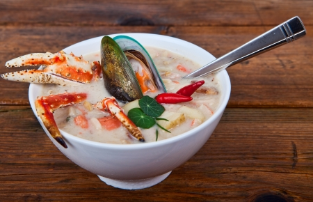 A bowl of sea food soup on a wooden background