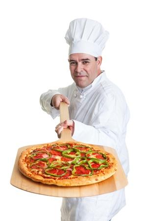 白い背景の上の炊きたてのピザを保持しているシェフ。