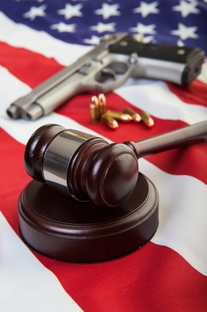 A wooden gavel on an american flag with a gun and bullets in the background, focus on the gavel.