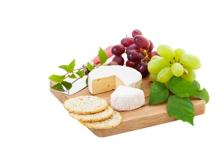 Brie Cheese and crackers with grapes on a white background