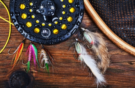 fly fishing: A fly fishing reel with flies and a landing net on a wet wooden background