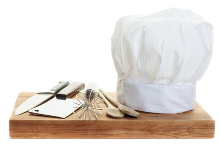 A chefs toque with various cooking utensils