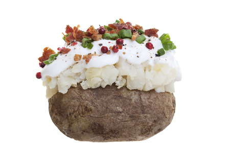 A stuffed baked potato with sour cream, bacon bits, and Green onions. Shot on a white