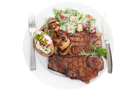 Grilled beef t bone steak dinner with caesar salad, mushrooms and rosemary