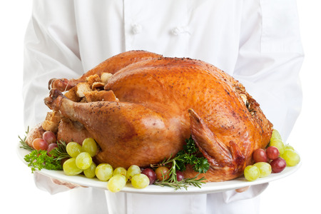 dinner jacket: Chef serving a stuffed turkey garnished with grapes.