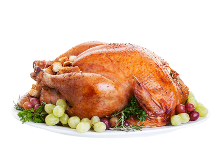 A large a stuffed turkey on a platter garnished with grapes.  photo