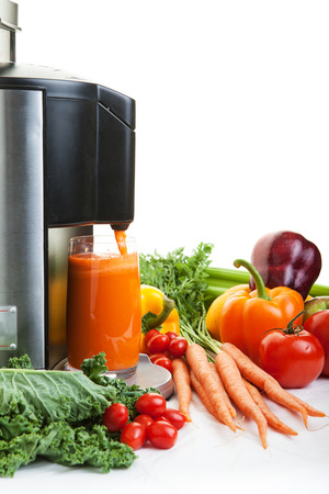 jugos: Un exprimidor rodeado de frutas saludables y verduras en blanco con sombras.
