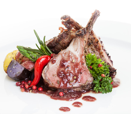 rack of lamb: Roasted Lamb Chops with Vegetables,potato and asparagus.focus on the front chop. Stock Photo