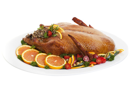 Roasted duck on a plate with salads oranges and vegetables,on a white background. photo