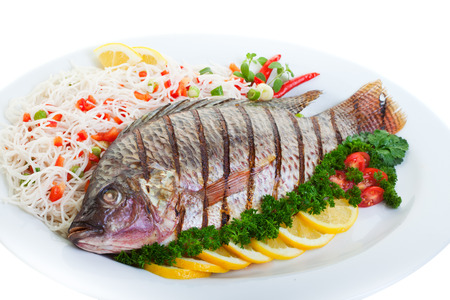 cooked fish: Grilled tilapia served with pasta and vegetables.