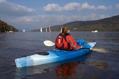 buoyancy: Mujeres remando kayaker lejos del espectador en el lago Windermere Inglaterra  Foto de archivo