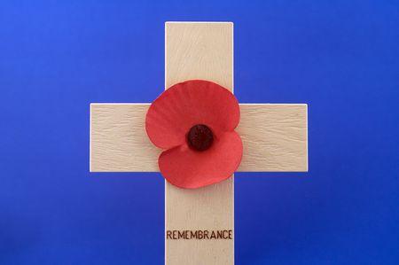 remembrance day poppy: Remembrance Day Poppy on wooden cross against blue background