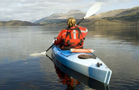 loch: Female kayaker paddling away from the viewer on Loch Lomond with Ben Lomond mountain in the background Stock Photo