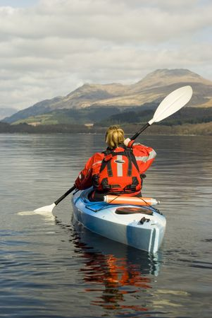 black white kayak: Female kayaker paddling away from the viewer on Loch Lomond with Ben Lomond mountain in the background Stock Photo
