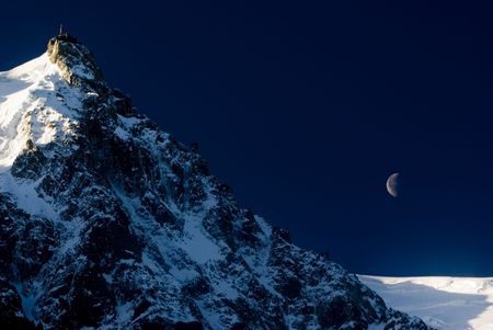 crevasse: View of Aiguille Du Midi from Chamonix at night with moon in background - landscape orientation