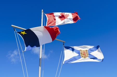 Canadian Flag Acadian Flag and Nova Scotia flag blowing in the wind against blue sky photo