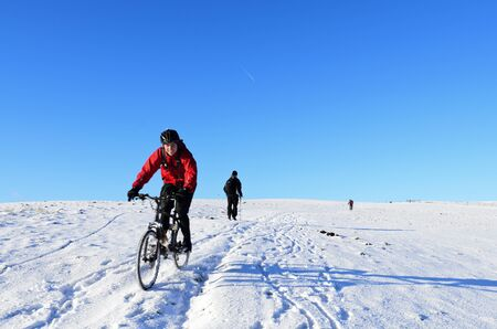 Hagg Side, England - December 18th, 2011: Unknown mountain biker and walker on snow covered hill above Ladybower Reservoir in Peak District National Park England