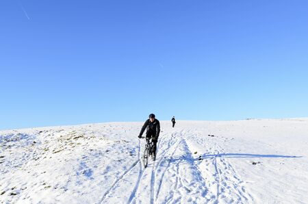 Hagg Side, England - December 18th, 2011: Unknown mountain biker and walker on snow covered hill above Ladybower Reservoir in Peak District National Park England Stock Photo - 11817019